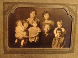 "Here's a studio portrait of my mom (bottom left, finger in nose), her two sisters (far right), some cousins, and an old woman whom Mom only remembers as ""Annie."" I get the impression that Annie's lap was a reliably safe place for the kids in my mom's family."