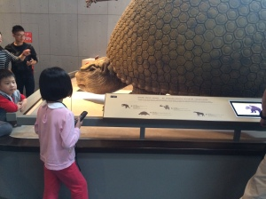 The ankylosaurus is whispering something in this little girl's ear.